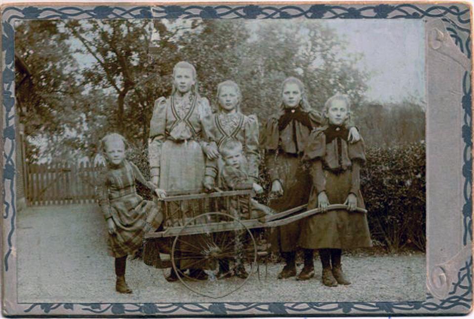 Deze foto van de jongedames de Wit is gemaakt op boerderij de Hoge Ham in 1904. Het kleine meisje naast de kar is de 4 jarige Jaantje en naast haar staat de 12 jarige Evertje. Daarnaast staan Leentje, Sien en Cor en in de kar zit Grietje, toen ongeveer 2 jaar oud.