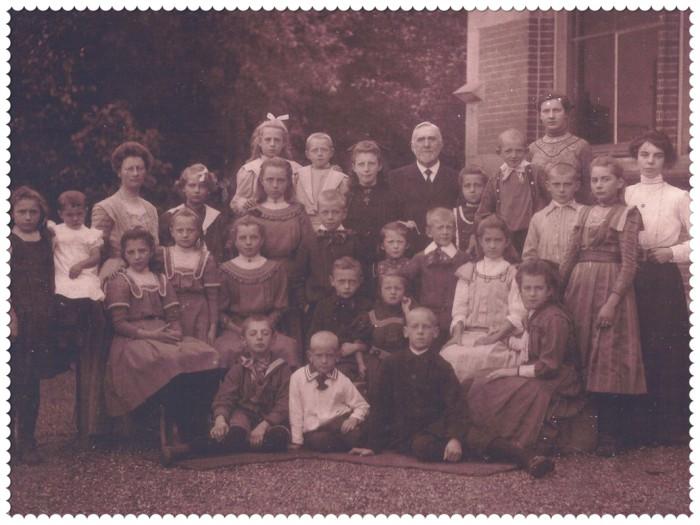 Schoolfoto van de openbare lagere school aan de Uitweg ter hoogte van de Rijnlaan in Harmelen. De foto werd vermoedelijk ergens in het voorjaar van 1910 gemaakt. Uiterst rechts op de achterste rij staat juffrouw Floortje Mingelen, iets verderop naar links staat meester Kroon en nog verder naar links staat juffrouw Jongens. Bij deze meester en juffen hebben kinderen van Adriana de Wit in de klas gezeten. Helemaal links op de 2e rij voor juffrouw Jongens zit Jaantje (Adriana Jannigje) Smit en naast haar staat Janna (Johanna) Smit. En het ventje dat voor ze op de grond zit met zijn ogen dicht is hun broertje Gert (Gerrit) Smit, toen 9 jaar oud.