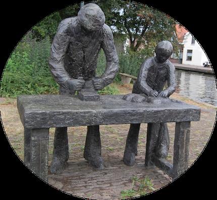 Beeldhouwwerk van een steenarbeider en zijn meewerkend kind. Het staat aan de Ouderijn - in het voormalige buurtschap Pannenbakkerijen - op de hoek Leidsestraatweg/Jozef Israellaan te Woerden. Ineke van Dijk, 1978.