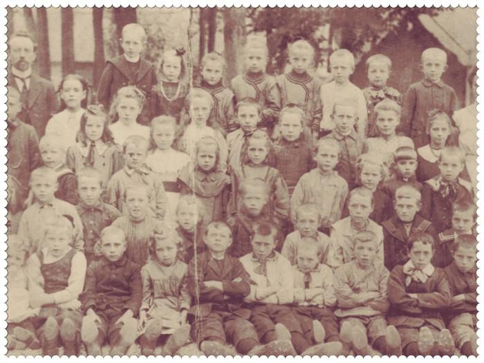 Schoolfoto van de hervormde school te Vleuten in 1912. De 10 jarige Grietje de Wit staat op de één na bovenste rij, ze is het tweede meisje van rechts. Ze staat naast een onbekende jongen en twee plaatsen naar links staat haar schoolvriend Pieter Lam. De drie meisjes achter hem met dezelfde kleding aan, zijn Pieters zussen Geertruida, Aaltje en Wijntje Lam (zij is de kleinste die het meest links staat). Helemaal links staat het hoofd van de school, meester Knopper. En op de voorste rij in het midden zitten twee jongen naast elkaar met witte bloesjes aan, dat zijn Arie en Nico van Selm (de kleinste), twee jongere broers van Dirk van Selm (B10.4).