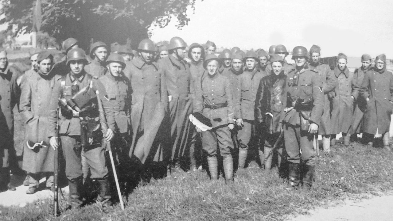 Een groep ontwapende Nederlandse soldaten die krijgsgevangen zijn genomen en onder bewaking staan van twee Duitse militairen. Deze foto werd genomen door een Duitse fotograaf in Rotterdam op 14 mei 1940 en gepubliceerd in 'Rotterdam Frontstad' van Gerard Groeneveld, uitgegeven in april 2016.
