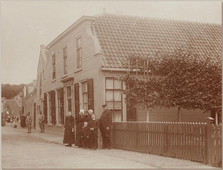 De Leidsestraatweg ter hoogte van nummer 41 in Woerden, met de woning en pakhuizen van graanhandelaar Jan van Doorn. Daarvoor staan van links naar rechts: Bregje van Doorn, haar grootmoeder Marrigje Bos, haar moeder Aaltje de Kruijf en haar vader Jan van Doorn. Op de voorgrond staan Willem en Hendrik van Doorn, de twee kleinzonen van Marrigje Bos. De foto werd omstreeks 1900 gemaakt.