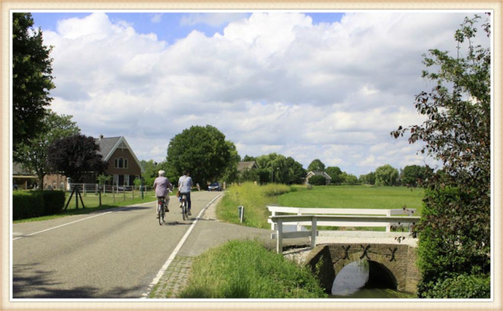 Foto met zicht op boerderij Welgelegen (links) Achtersloot 75 in IJsselstein. Deze langhuisboerderij werd omstreeks 1889 gebouwd, op de plek van voorgangers. Vandaaruit wordt uitgekeken op de tegenoverliggende Noord IJsseldijk (rechts gelegen). Op een gevelsteen in de voorgevel staat het opschrift: 'De eerste steen gelegd door J. Bos en M. van Brughem'. Daaronder zit een oudere steen met de tekst: 'YYB 1815' (2).